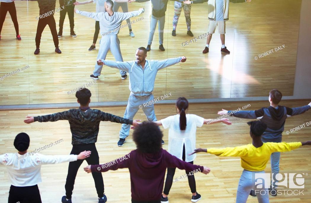 Stock Photo: Male instructor leading dance class in studio.