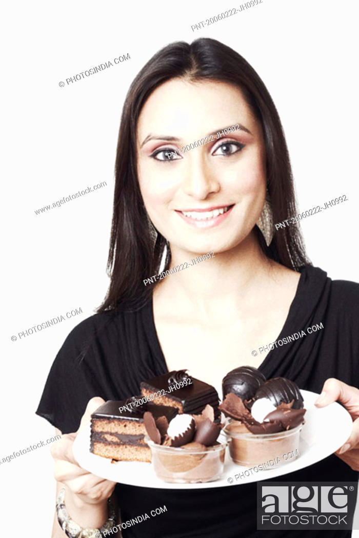 Stock Photo: Portrait of a young woman holding a plate of pastries and chocolate ice-cream.