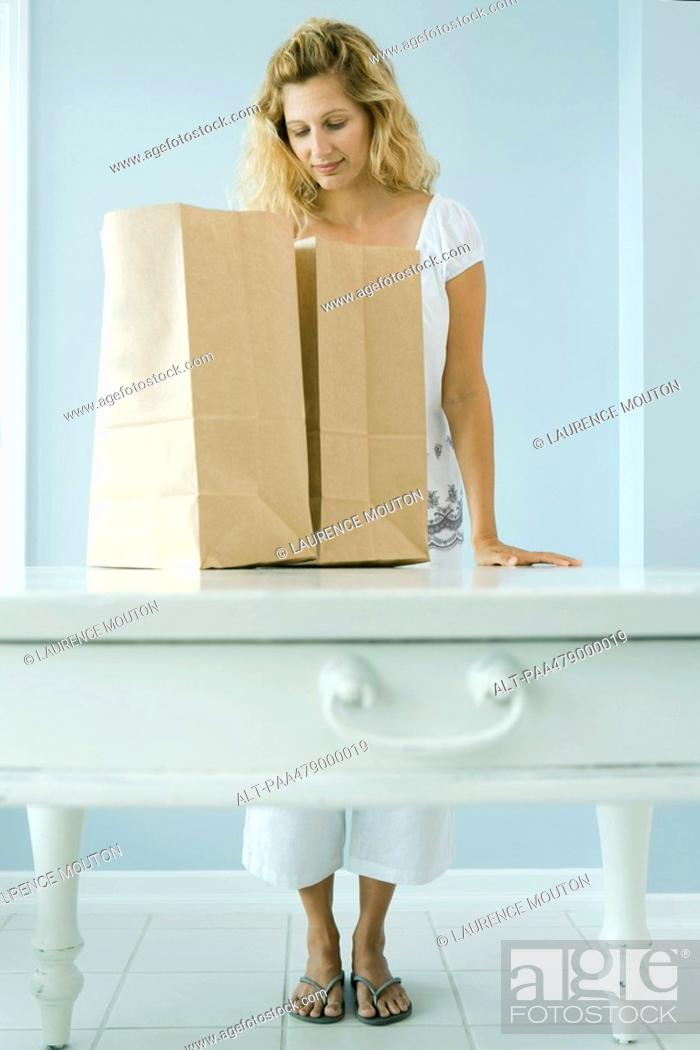 Stock Photo: Woman looking into grocery bag.