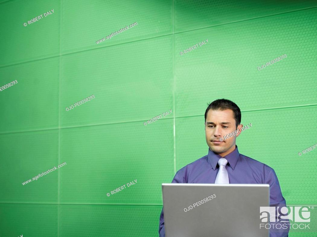 Stock Photo: Businessman with laptop in green office.