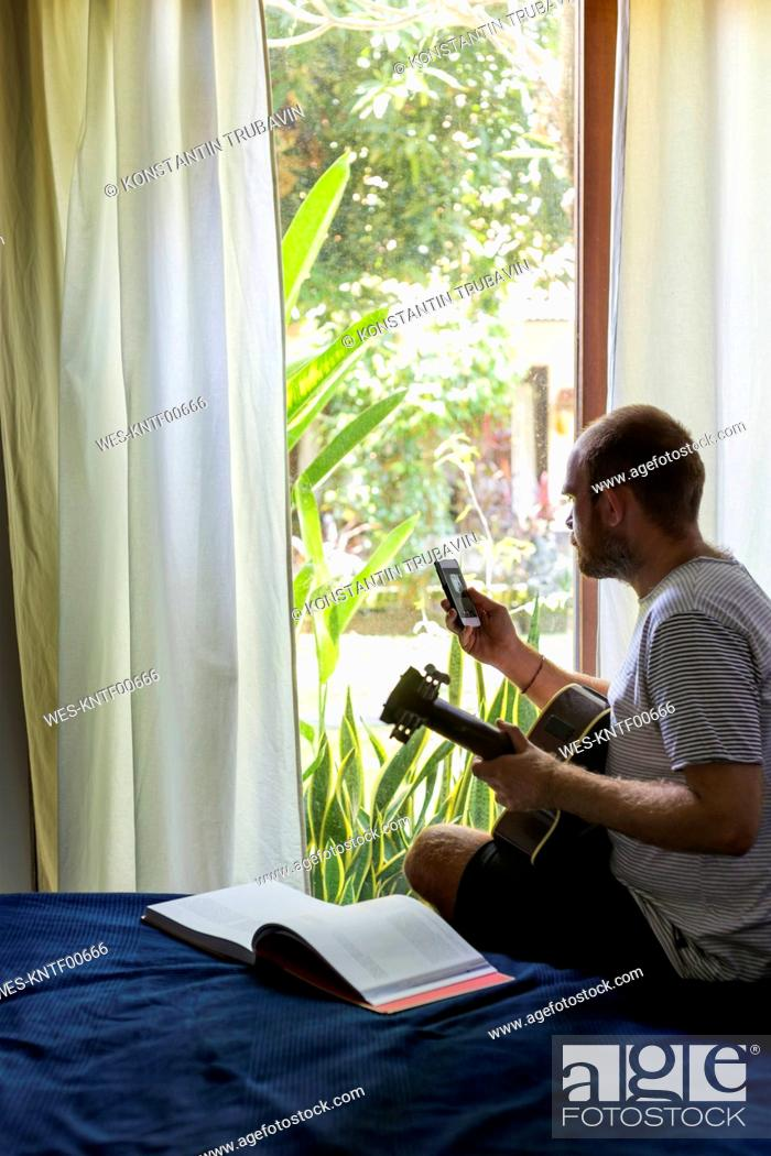 Imagen: Man with guitar and cell phone sitting on bed.