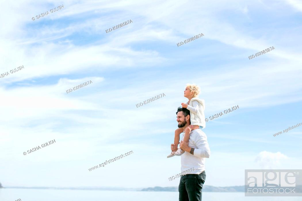 Stock Photo: Mature man giving daughter a shoulder carry at coast.