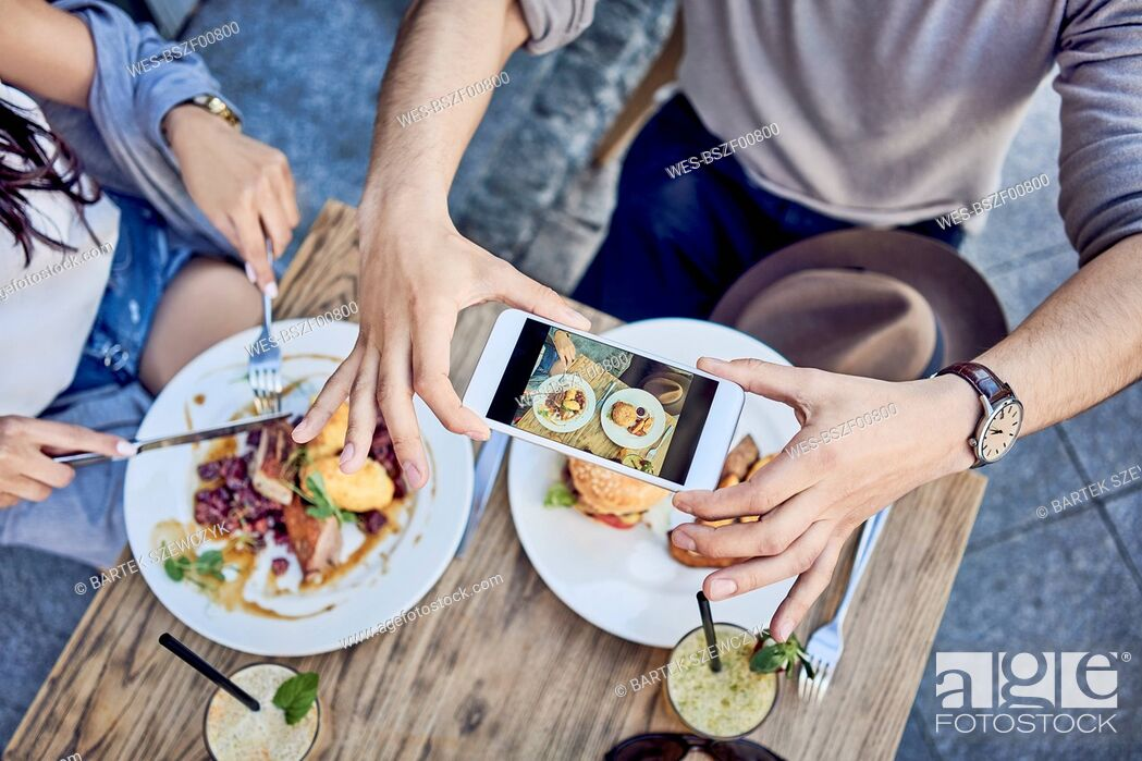Imagen: Overhead view of couple taking photo of food at outdoors restaurant.
