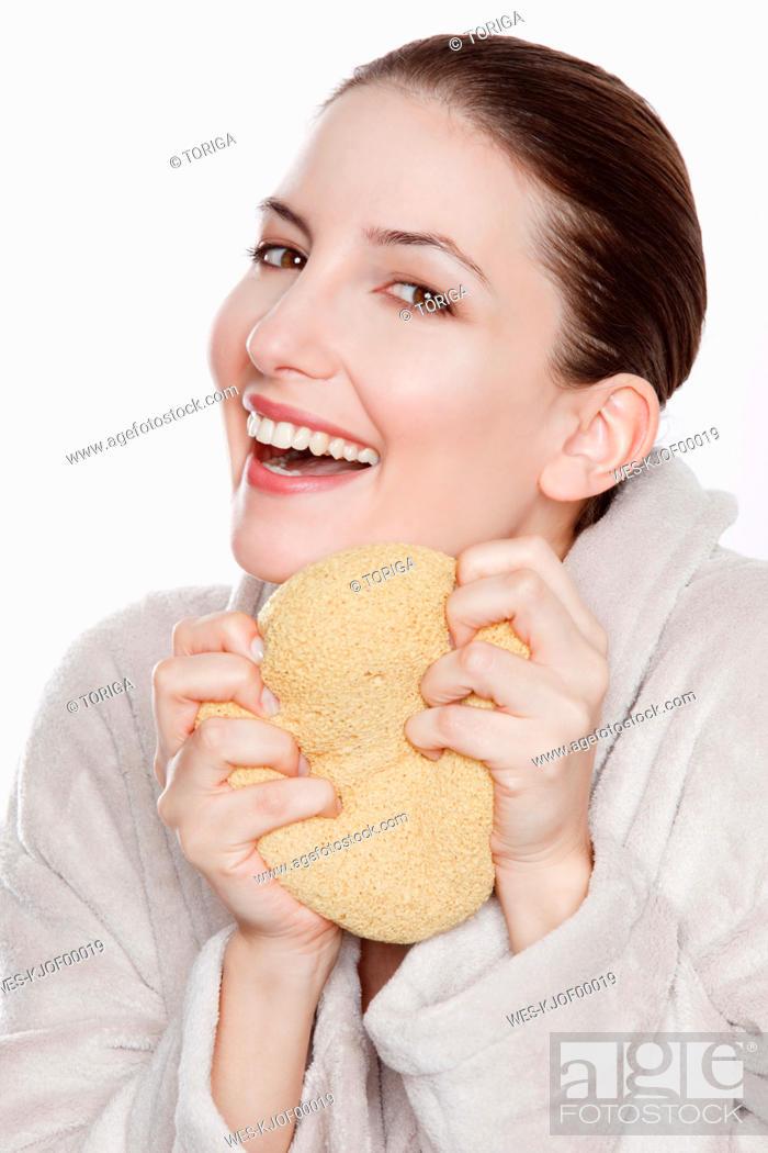 Stock Photo: Woman in bathrobe holding sponge, smiling, portrait.