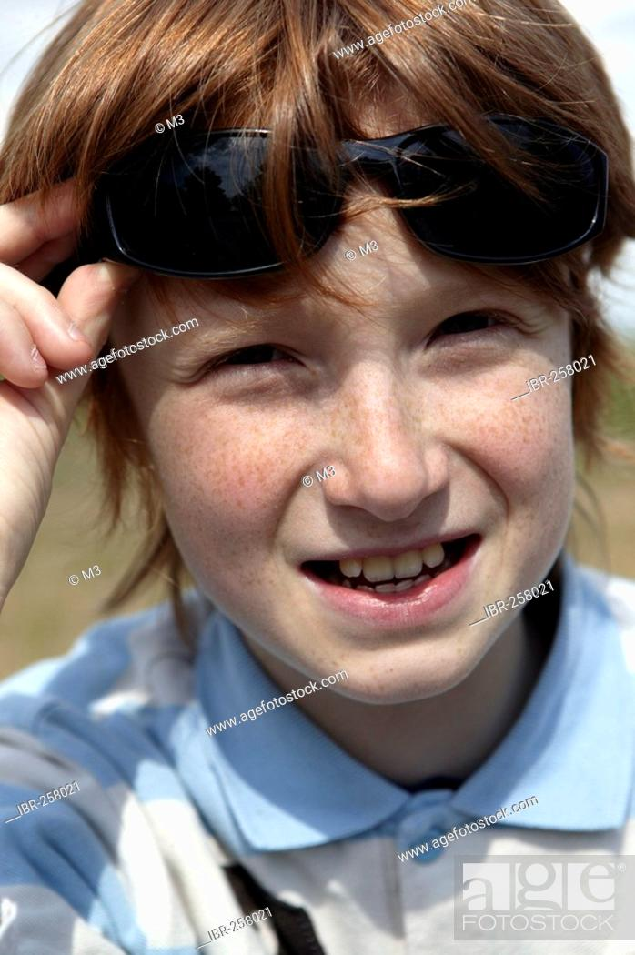 bad730147d51 Red-haired smiling boy, 11 years old with sunglasses, Stock Photo ...