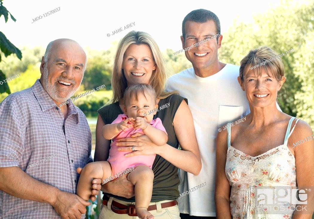 Stock Photo: Baby girl with parents and grandparents in garden.