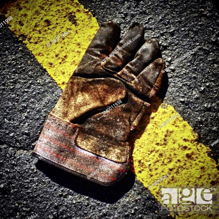 Stock Photo: An old work glove on the ground.