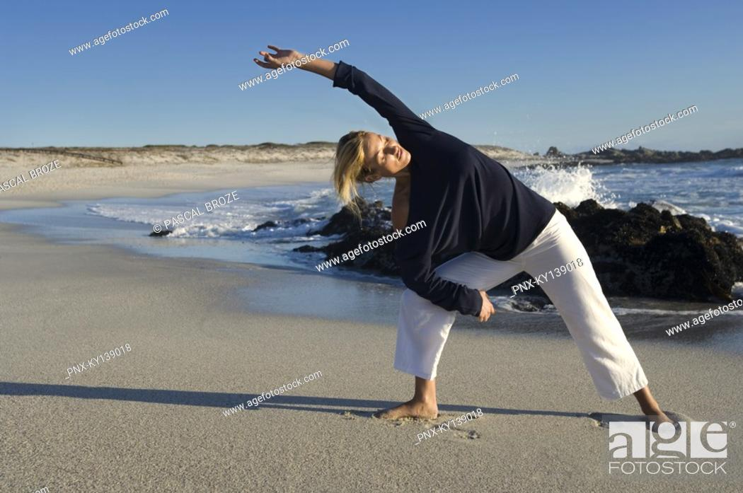 Stock Photo: Young woman stretching on the beach, outdoors.