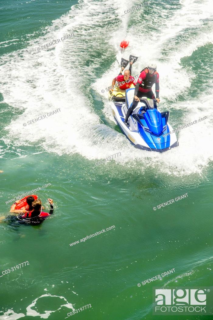 Stock Photo: A rescue water craft arrives for a drowning victim and a lifeguard in Huntington Beach, CA.