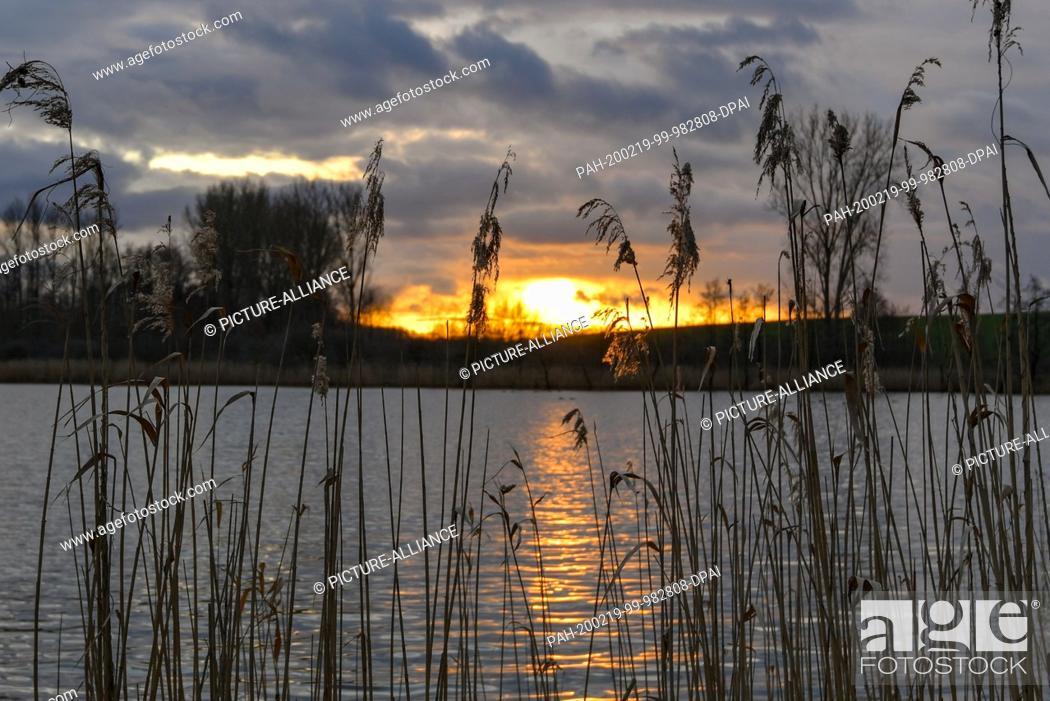 Stock Photo: 19 February 2020, Brandenburg, Falkenhagen: The sunset glows in a colourful way between dark rain clouds over the Gabelsee in the district of Märkisch-Oderland.