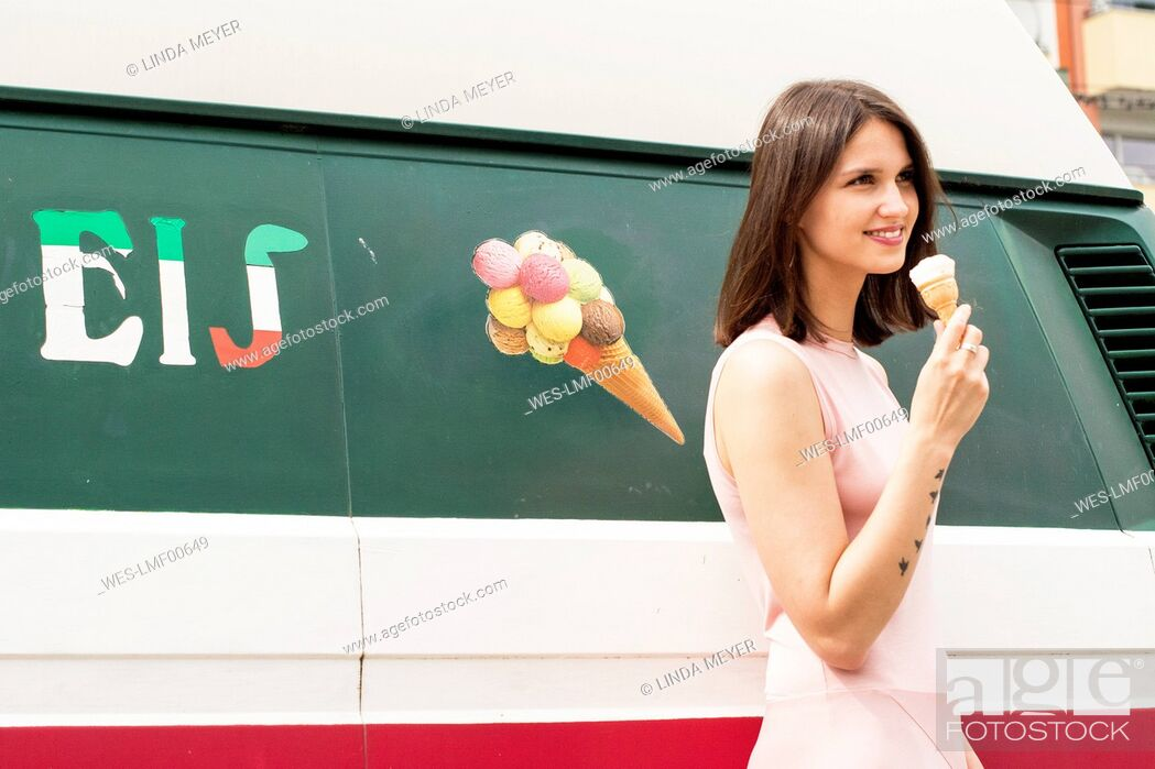 Stock Photo: Smiling young woman with ice cream cone in front of ice cream van.