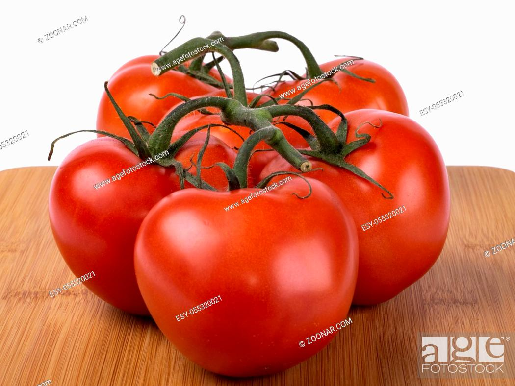 Stock Photo: red tomatoes on a twig, lie on a wooden board, image on a white background.