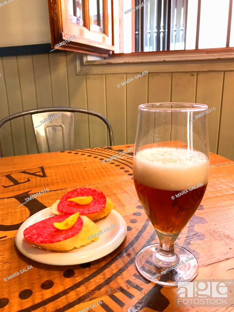 Stock Photo: Glass of beer with tapa. Spain.