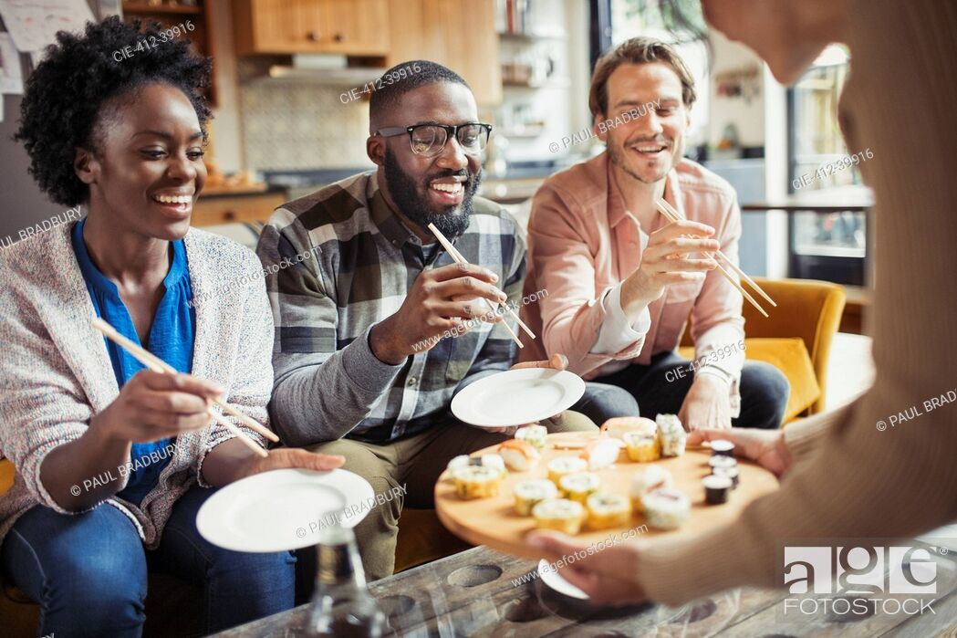 Stock Photo: Friends eating sushi in living room.