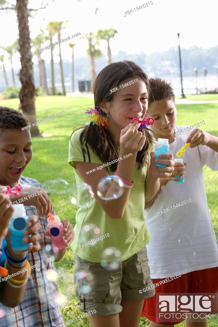 Imagen: Children blowing bubbles at a park.