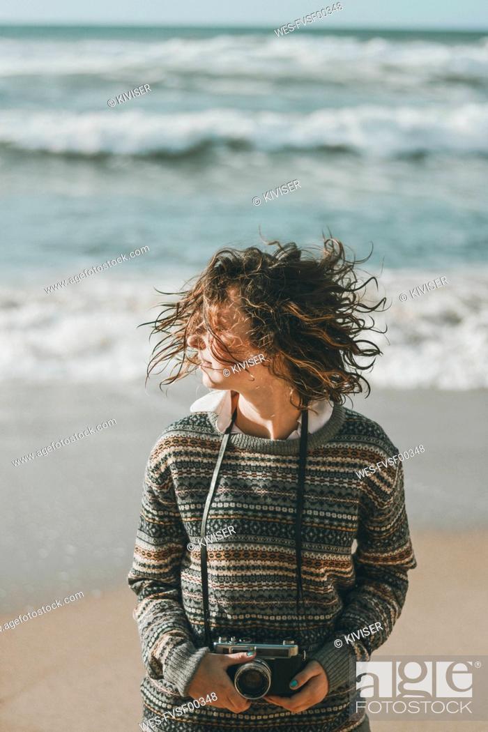 Imagen: Young woman standing with tousled hair against sea, Praia da Ursa, Lisboa, Portugal.