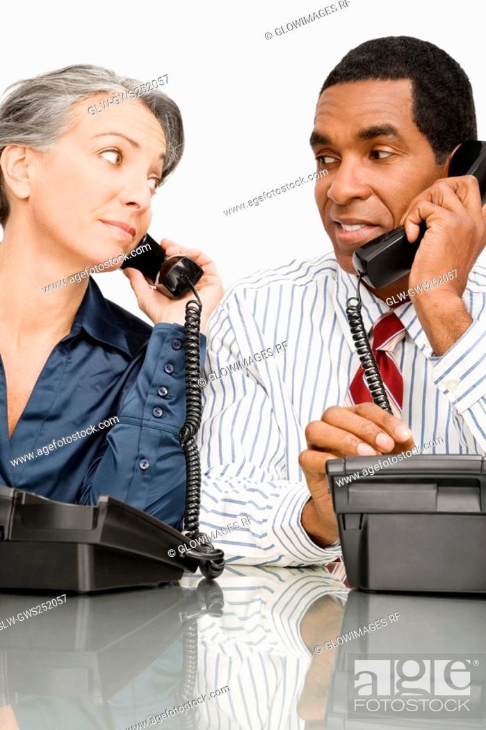 Stock Photo: Businessman and a businesswoman talking on landline phones.