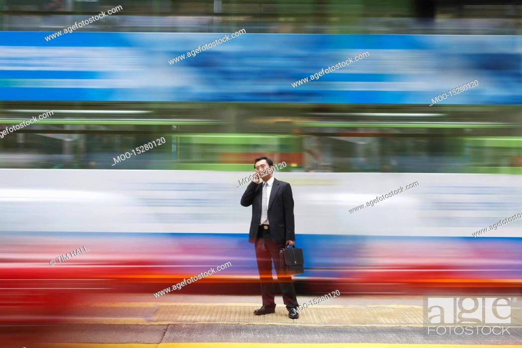 Stock Photo: China Hong Kong business man using mobile phone standing on street long exposure.