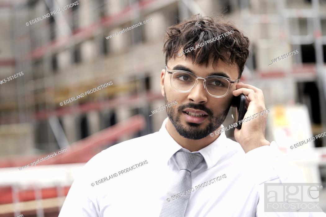 Photo de stock: Businessman on building site, talking on phone.
