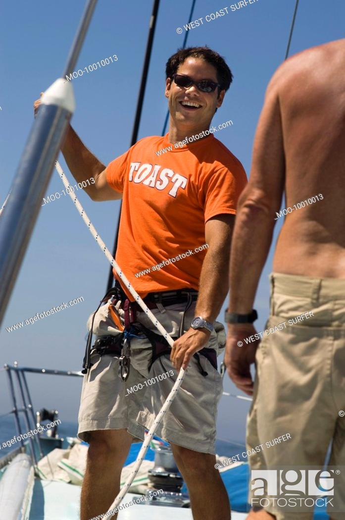 Stock Photo: Smiling Sailor Working Ropes on Yacht portrait.