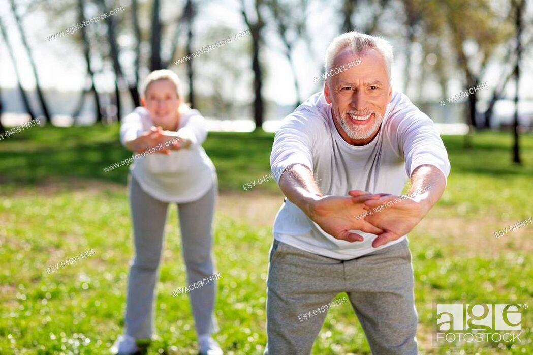 Imagen: Useful exercise. Cheerful aged man leaning forward while doing exercises.