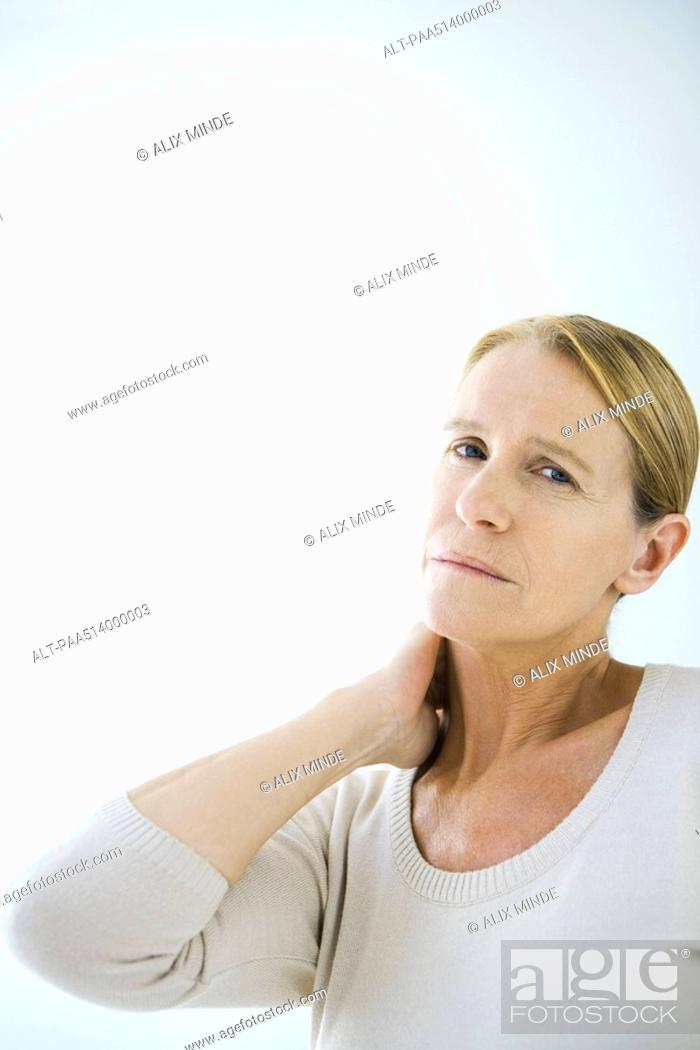 Stock Photo: Mature woman rubbing her neck, looking at camera.