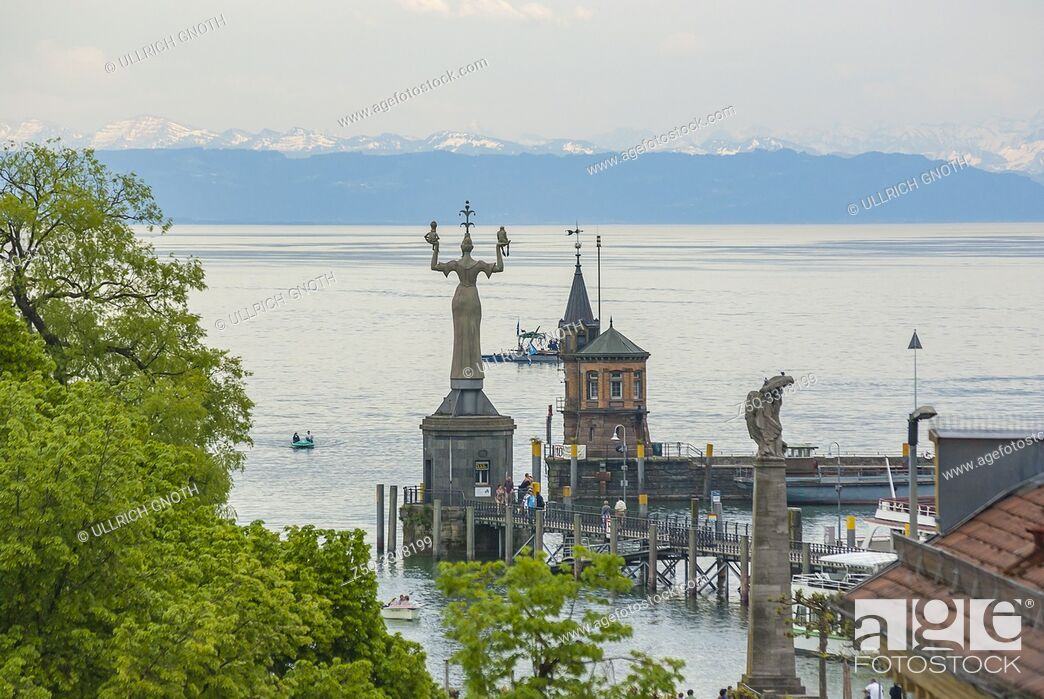 Stock Photo: View over the lighthouse and the statue of the Imperia by Peter Lenk, as well as the Zeppelin memorial in the harbour of Konstanz at Lake Constance.