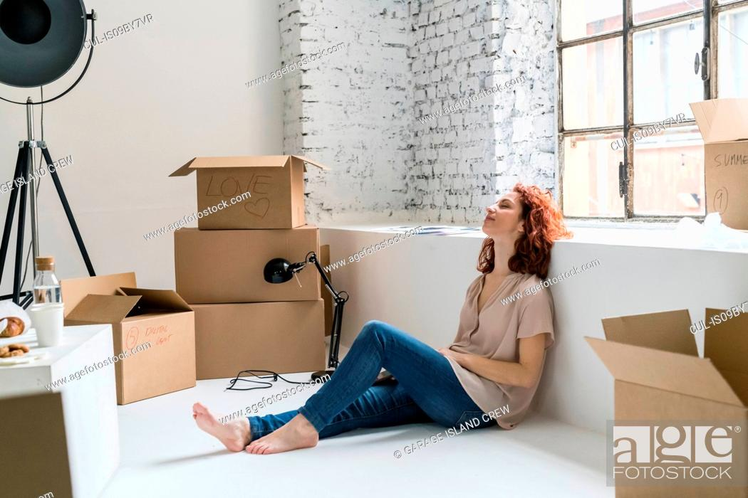 Imagen: Mid adult woman sitting on floor relaxing, moving into industrial style apartment.