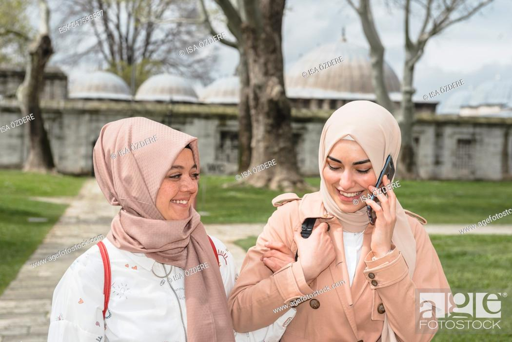 Stock Photo: Beautiful Muslim women in headscarf and fashionable modern trendy clothes walk and chat together while having fun. Modern Muslim women lifestyle travel tourist.