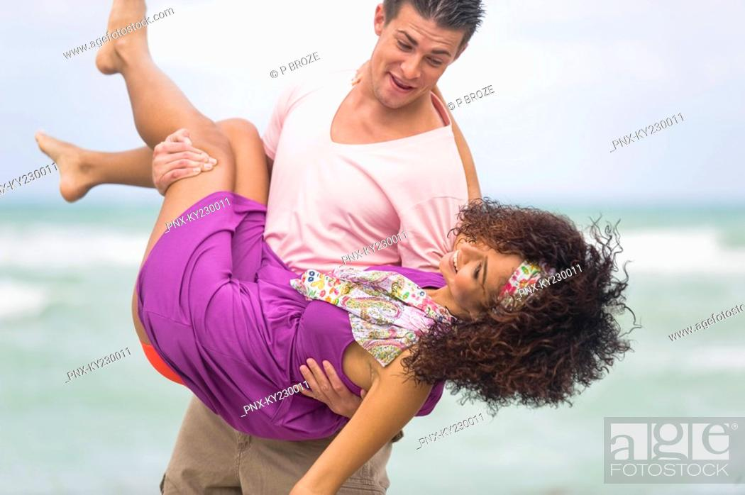Stock Photo: Man carrying a woman on the beach.
