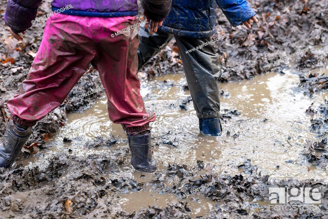 Stock Photo: Young children playing in a muddy puddle.