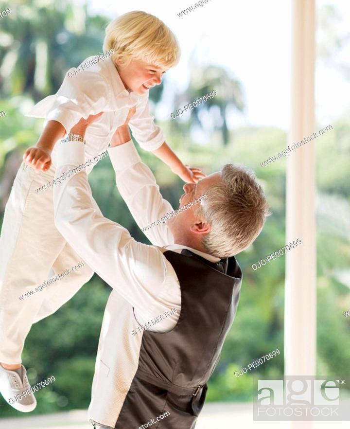 Stock Photo: Father lifting son.