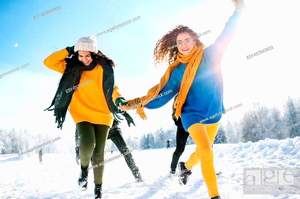 Stock Photo: A group of young cheerful friends on a walk outdoors in snow in winter forest, holding hands and running.