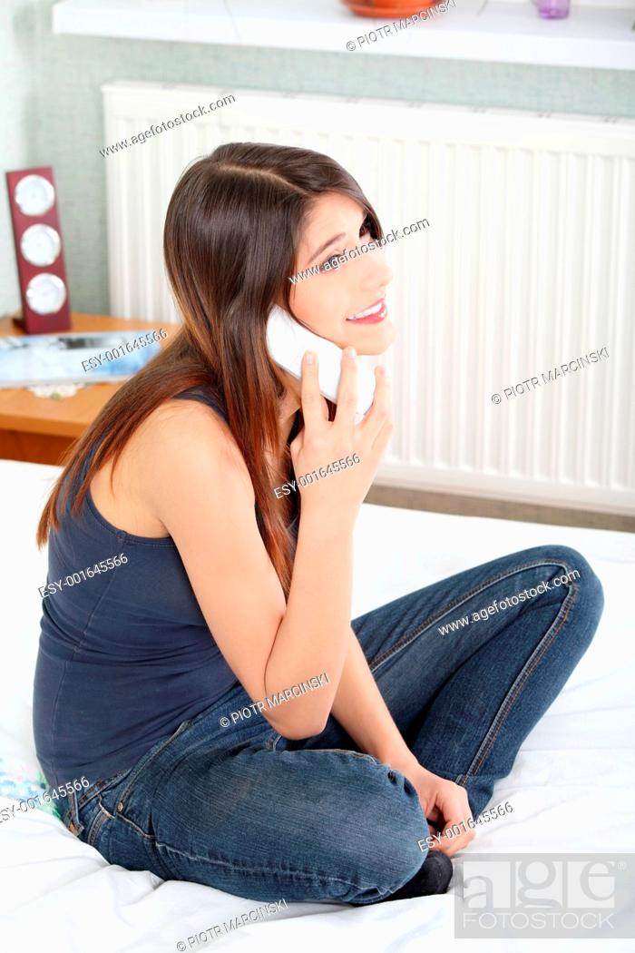 Stock Photo: Pretty woman with phone sitting on bed.