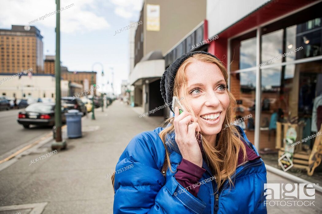 Stock Photo: Young woman talking on her smartphone in downtown Anchorage, South-central Alaska; Anchorage, Alaska, United States of America.