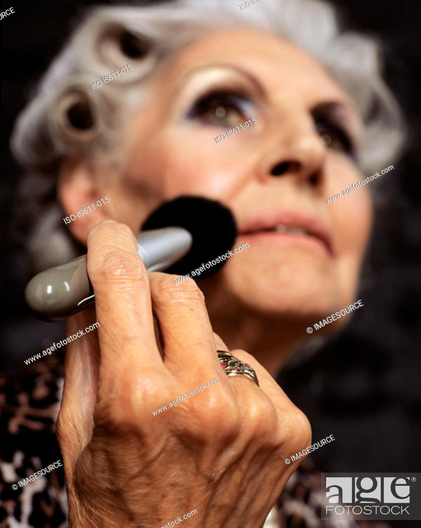 Stock Photo: Senior woman applying makeup.