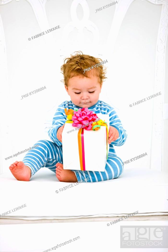 Stock Photo: Baby boy holding a present in an armchair.