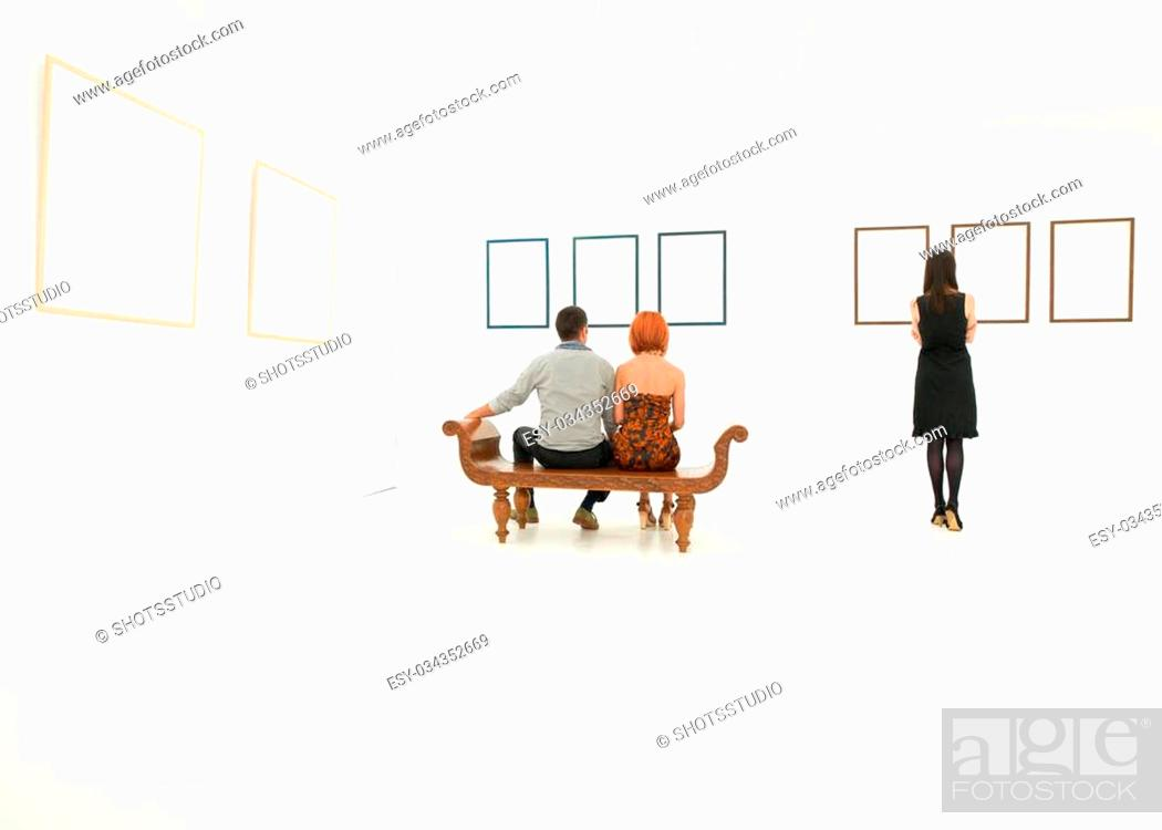 Imagen: back view of three young caucasian people looking at empty frames on white walls.