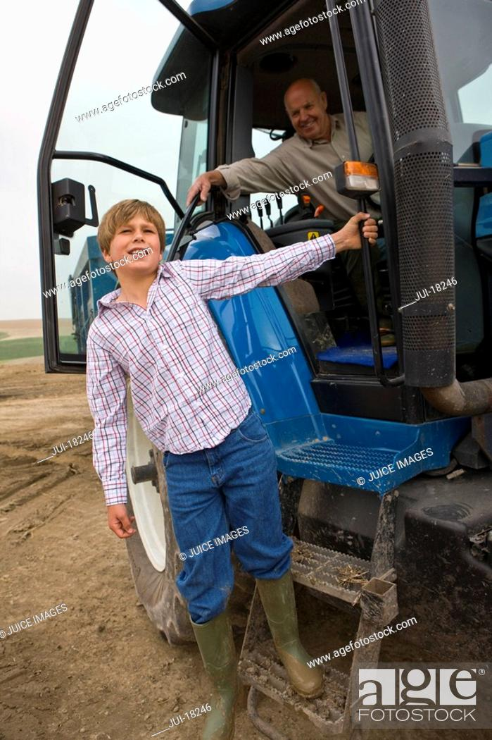 Stock Photo: Boy leaning out of tractor.
