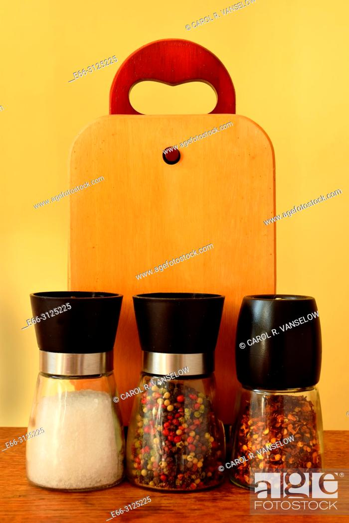 Stock Photo: Shakers of sea salt, pepper and red peppers sitting on table.