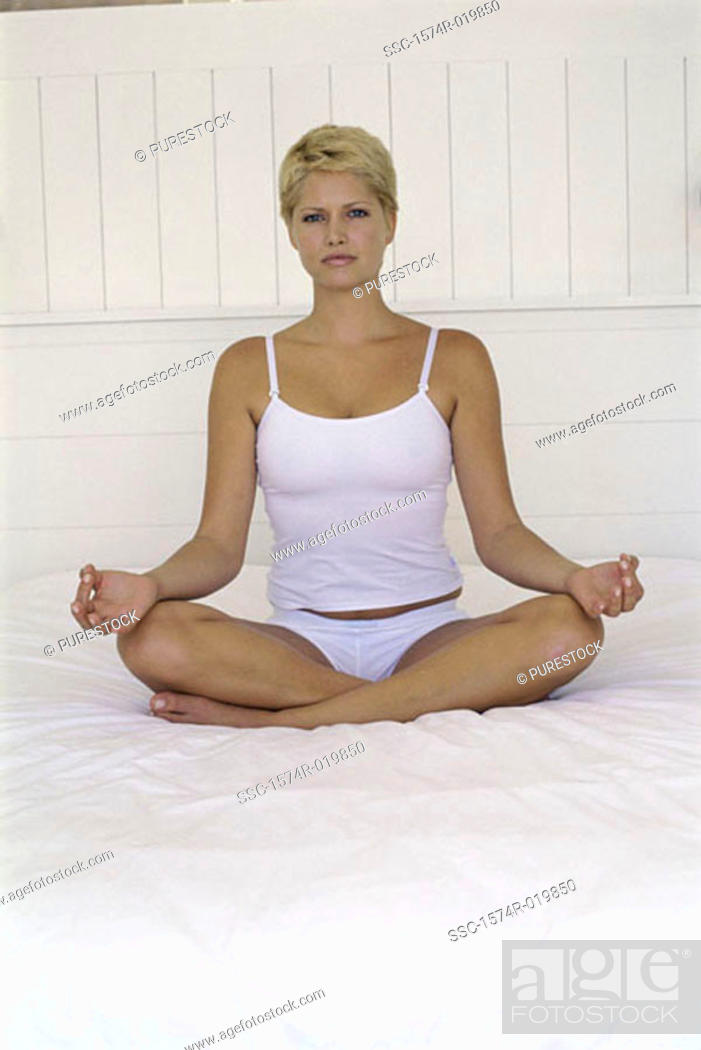 Stock Photo: Portrait of a young woman sitting in a lotus position.