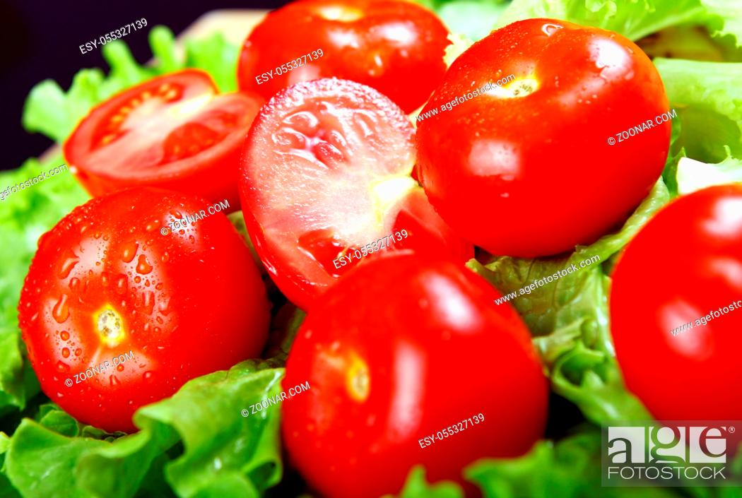 Stock Photo: Fresh and wet tomatoes lying on the salad leaves.