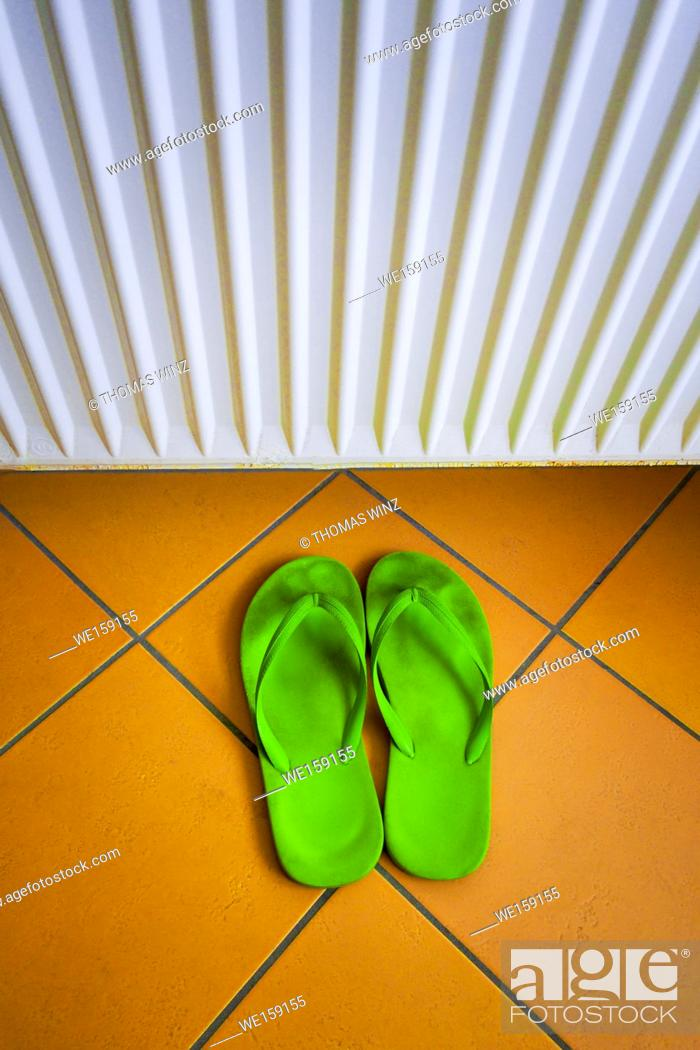 Stock Photo: green slippers on a tiled bathroom floor with a radiator on the wall , Stuttgart , Germany.