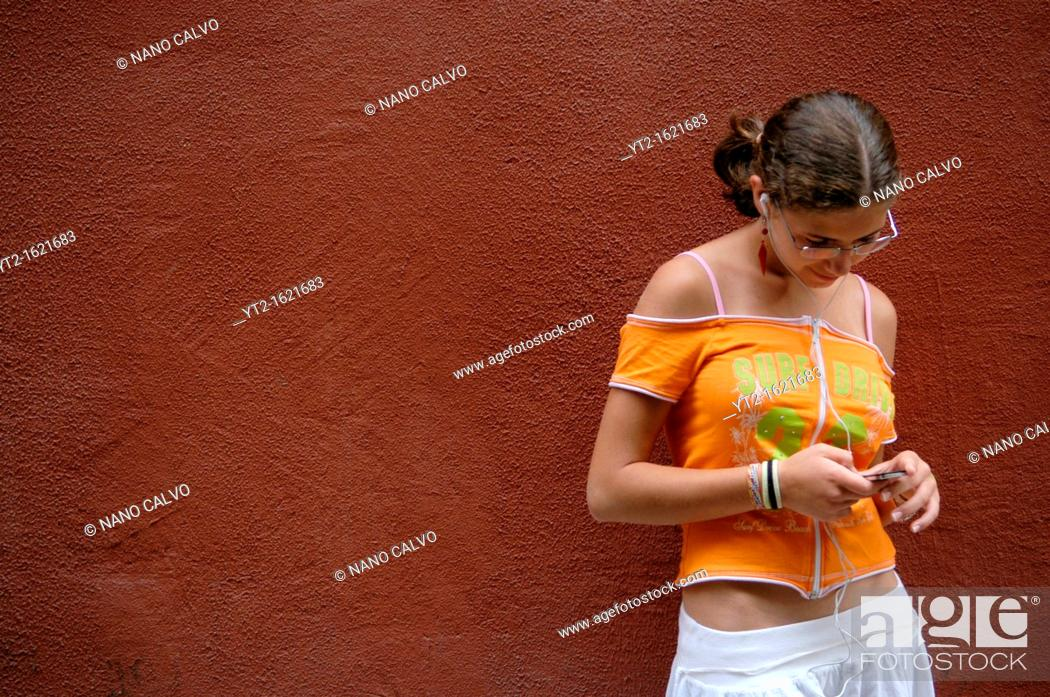 Stock Photo: Cute Spanish teenager listening to music on her iPod.
