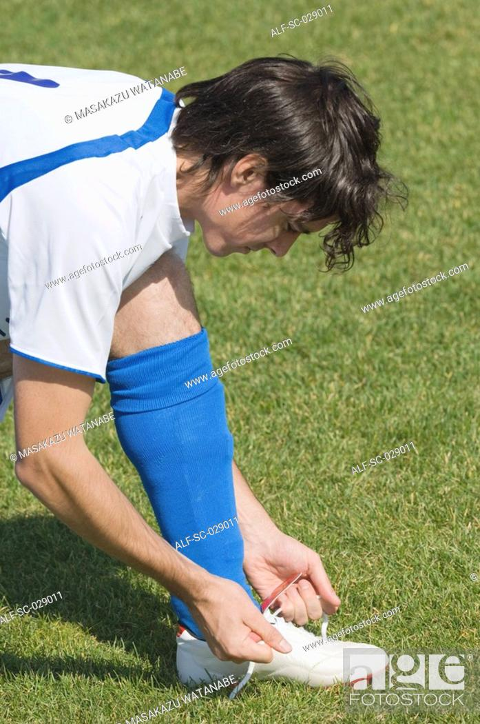 Stock Photo: Soccer Player Tying His Boot.