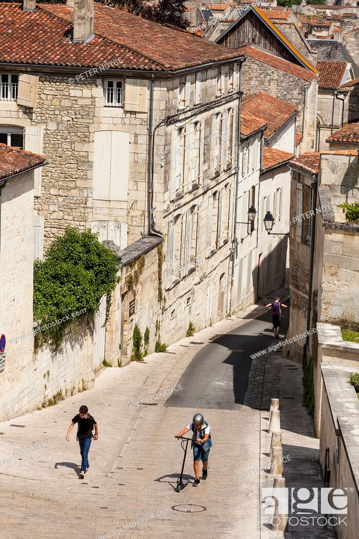Stock Photo: Two boys walking up the steep hill of Rue des Jacobins in Saintes.