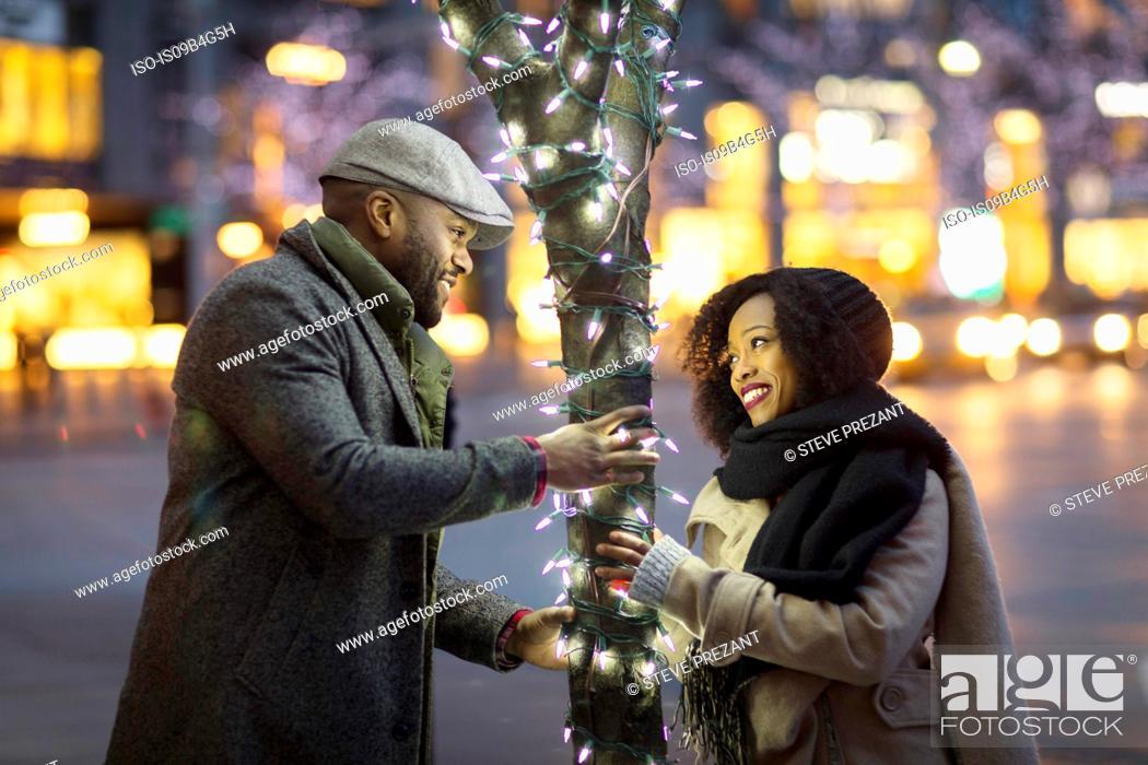 Stock Photo: Couple having fun by illuminated tree in city at night, New York, USA.