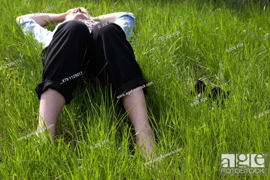 Stock Photo: middle aged man wearing suit trousers shirt and tie lying in long grass relaxing with shoes and socks off.