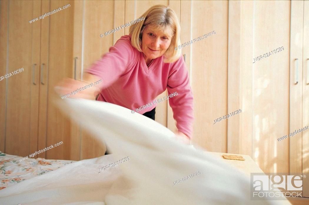 Stock Photo: elderly woman changing the linen.