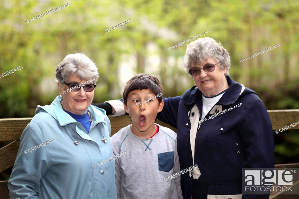 Stock Photo: Multi-racial grandson with elderly twin sisters - shallow depth of field.